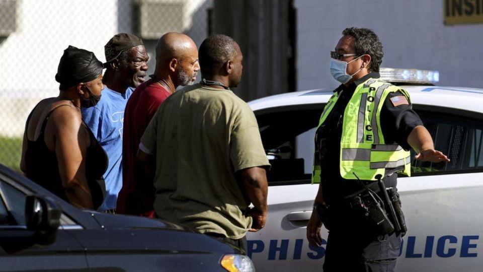 Familiares de las víctimas esperan con los oficiales en las inmediaciones de la Oficina de Servicio Postal (Foto: AP)