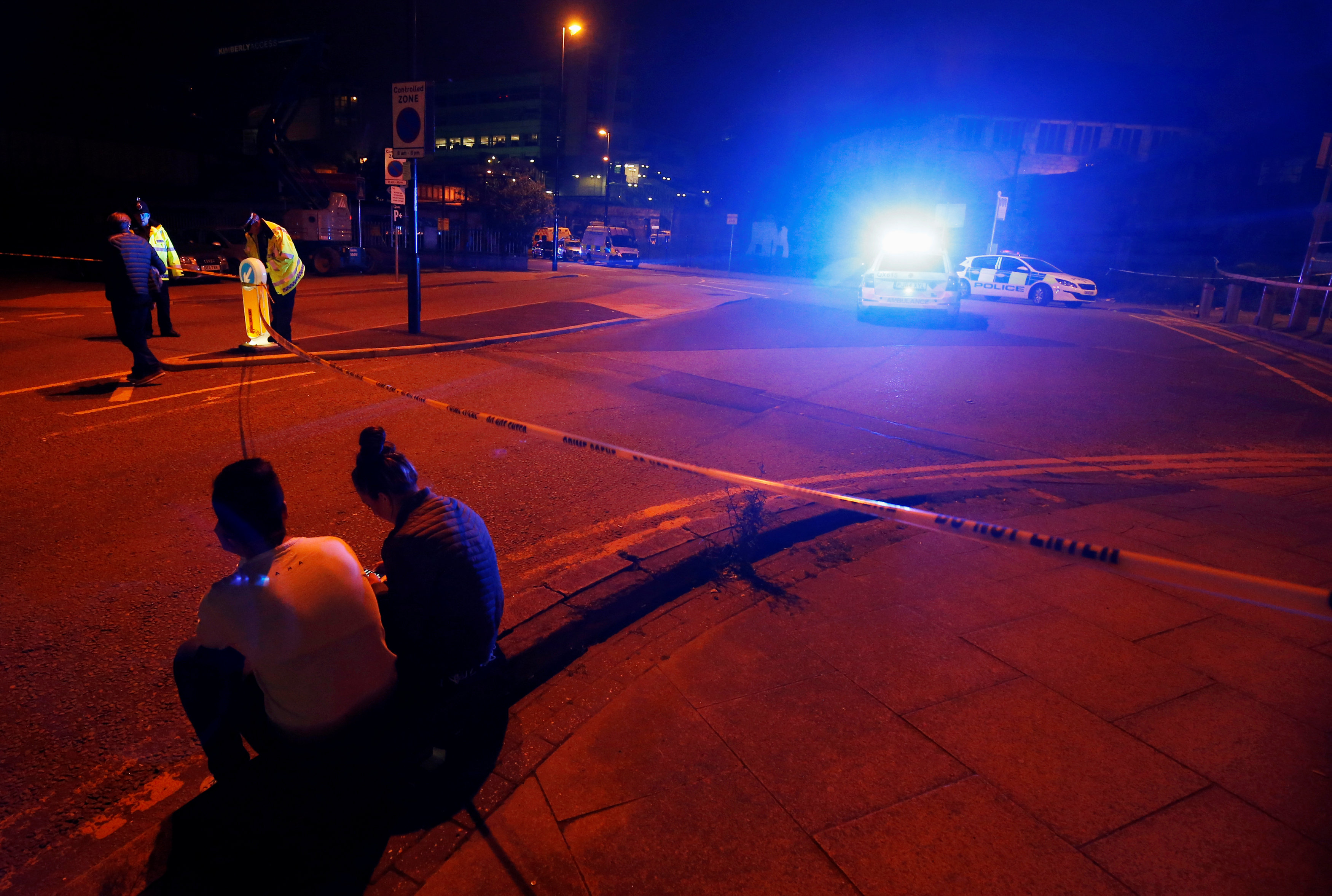 Personas sentadas cerca de la policía afuera del Manchester Arena. REUTERS/Andrew Yates
