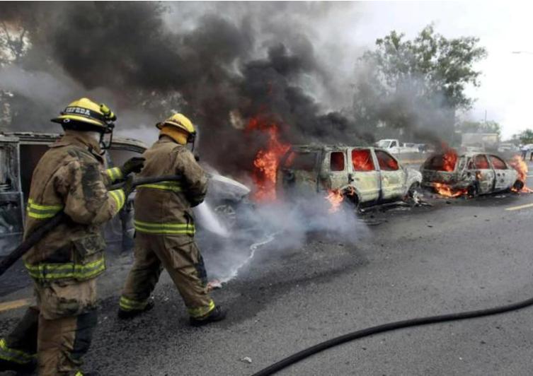 Bomberos apagando automóviles incendiados. Foto: Reuters.